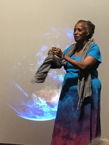 Woman in turquoise standing in front of image of Earth
