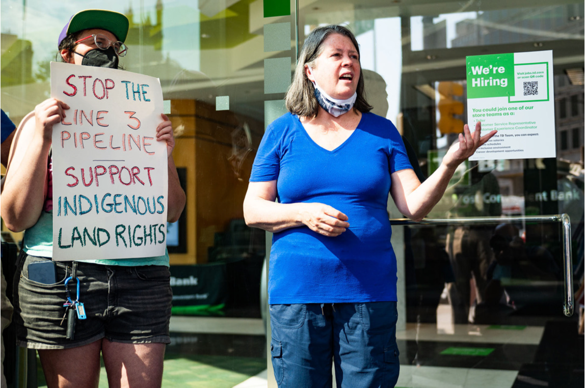 """Person with glasses, hat and mask holds sign that says """" Stop the Line 3 Pipeline, Support Inndigenous Rights"""" next to a white woman in a blue shirt, speaking."""