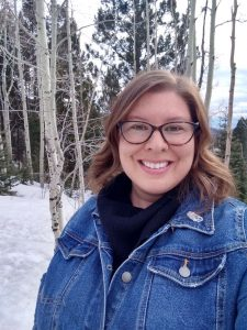 Woman in jean jacket and glasses standing in front of snow and trees