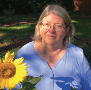 Woman in grey top standing beside sunflower