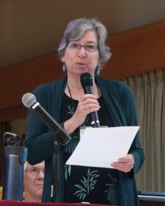 Woman in green and black with glasses speaking into microphone