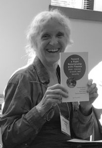 Black and white photo of woman smiling and holding a book