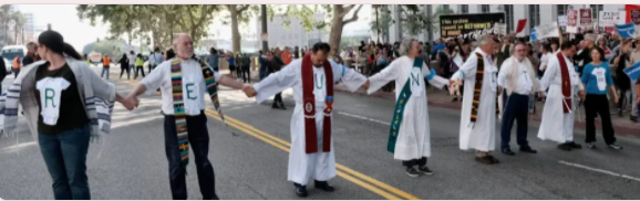 [This photo is from an action in southern California, where clergy took a stand against family separation at the US-Mexico border.]