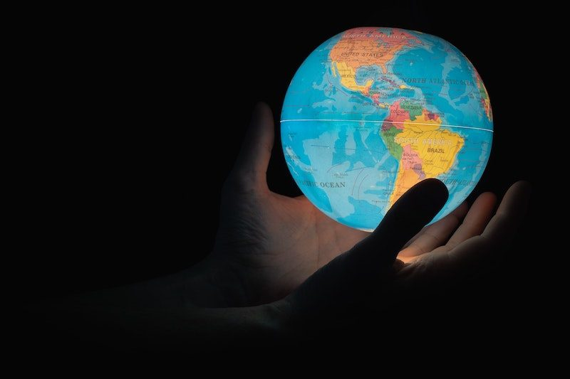 Shadow hands holding lit globe in their hands