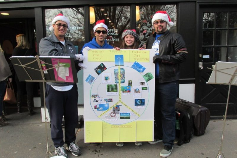 Group of four people with sign