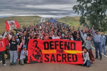 """Hundreds of people with red sign that says """"Defend the Sacred"""""""