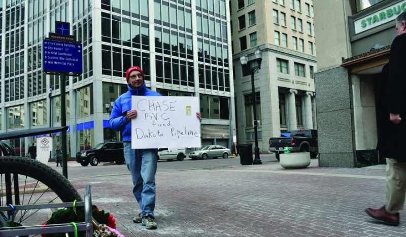 Man holding sign outside of Chase bank
