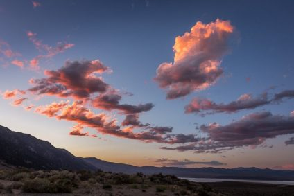 Pink sunset clouds above mountains