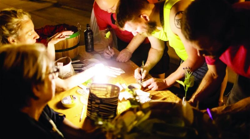Group of people writing no leaves under a light