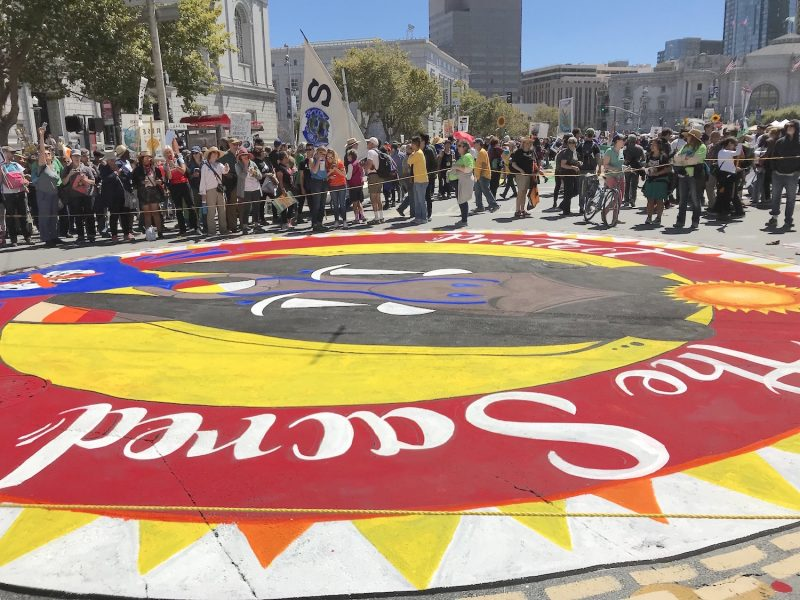 """A red circle that says """"Sacred"""" painted on the ground with a group of people in the background in San Francisco"""