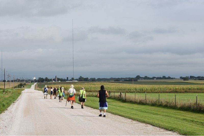 A few people walking ona very straight, flat highway