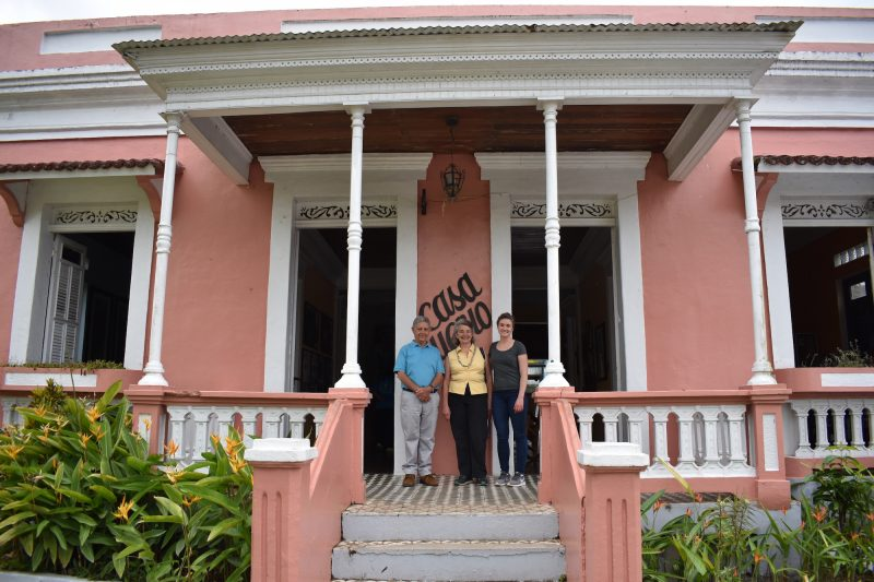 Three people stand in front of light pink house with porch