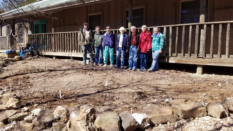 Seven people stand in soil