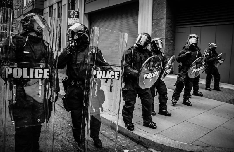 Black and white photo of six police officers in Washington DC in riot gear