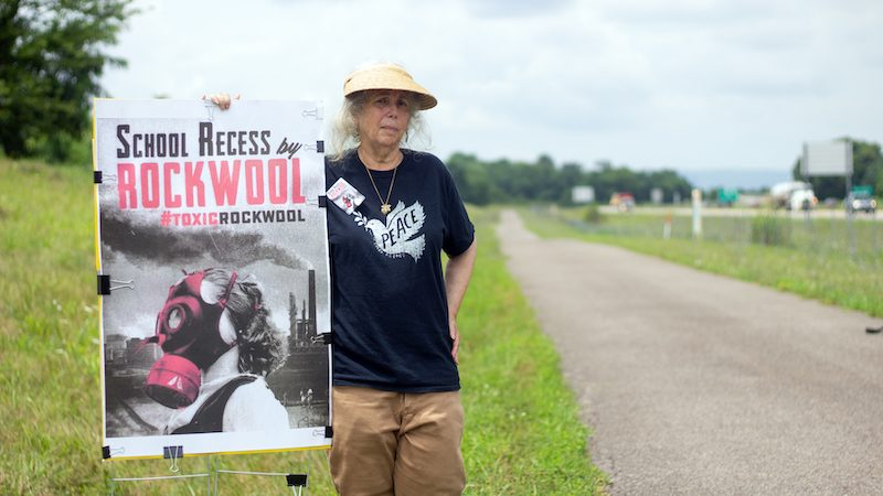 Bobbi Block holding up Rockwool protest poster next to country road