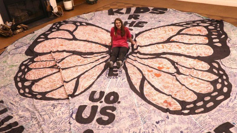 Kallan Benson sits on her butterfly parachute