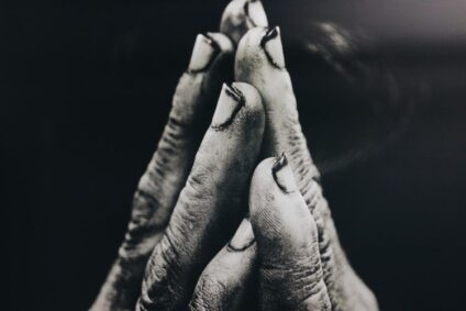 Black and white photo of two hands coming together