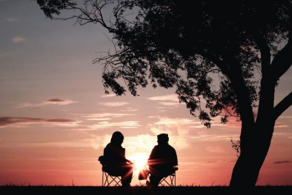 Two people backlit by pink sunset sitting in chairs under a tree