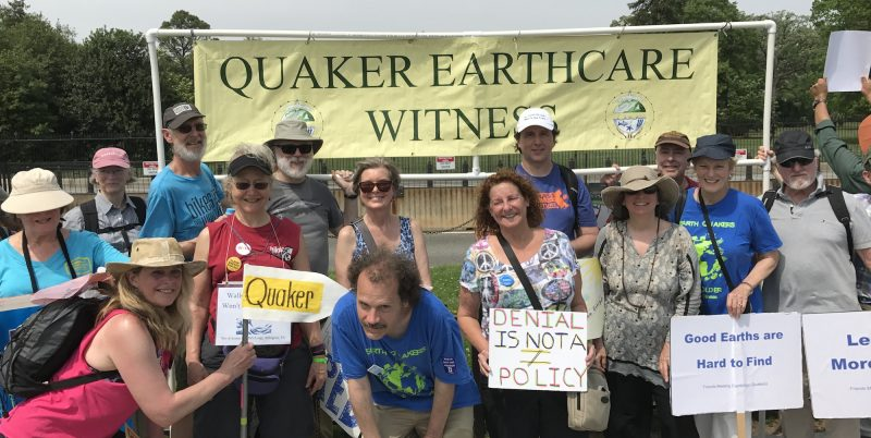 Smiling group of people in front of Quaker Earthcare Witness sign