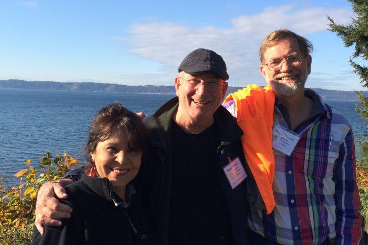 Three smiling people in front of ocean