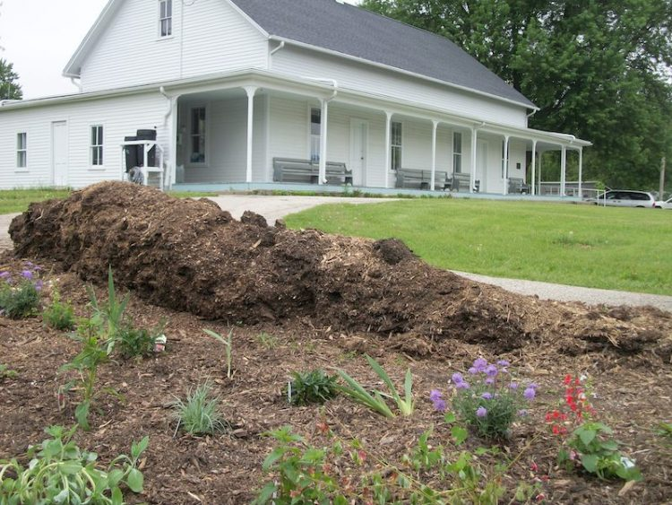 White meetinghouse with beginning garden in foreground