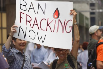 Two people holding sign that says Ban Fracking Now