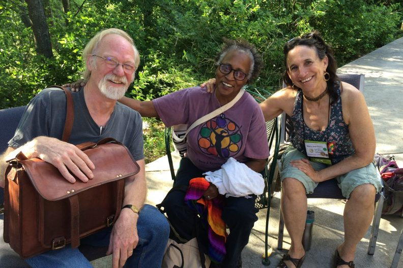 Three smiling people sitting in chairs outside