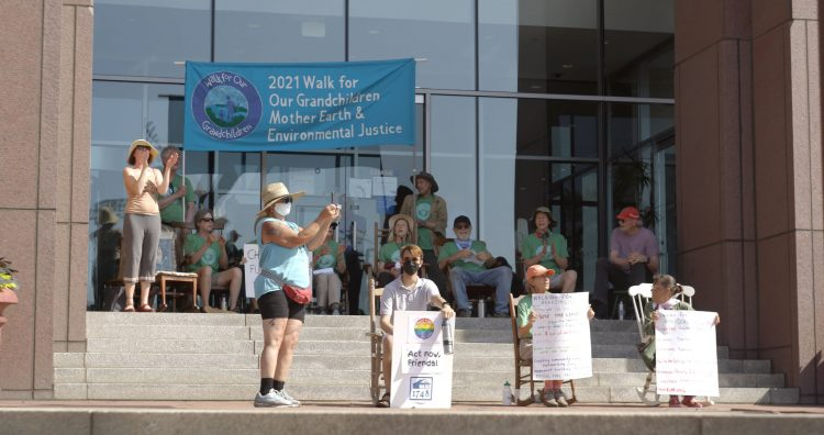 Twelve people sitting in rocking chairs or standing and clapping standing on steps in front of a bank. Sign in background says 2021 Walk for Our Grandchildren, Mother Earth, and Environmental Justice
