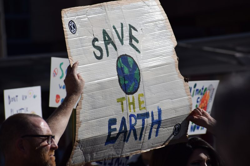 """Man with glasses holding up cardboard sign that says """"Save the Earth"""""""